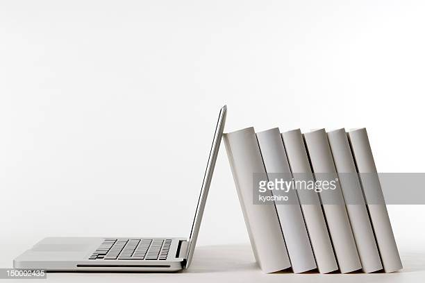 Isolated shot of laptop leaning blank books on white background