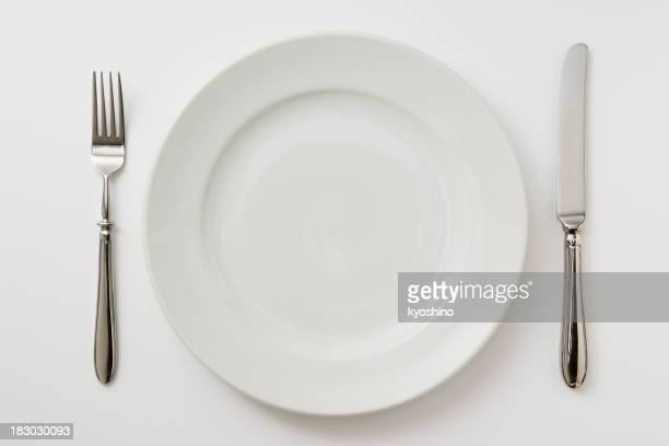 Isolated shot of plate with cutlery on white background