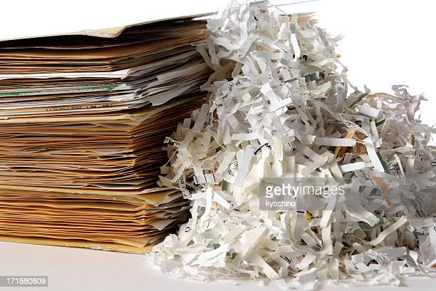 Isolated shot of shredded documents with folder on white background
