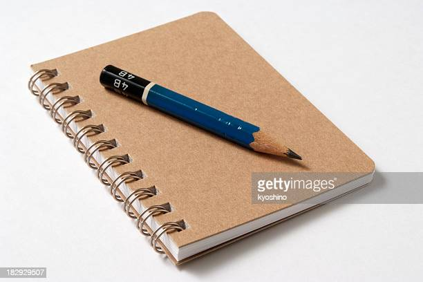 Isolated shot of spiral notebook with pencil on white background