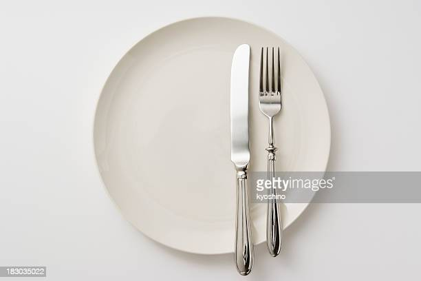 Isolated shot of white plate with silverware on white background