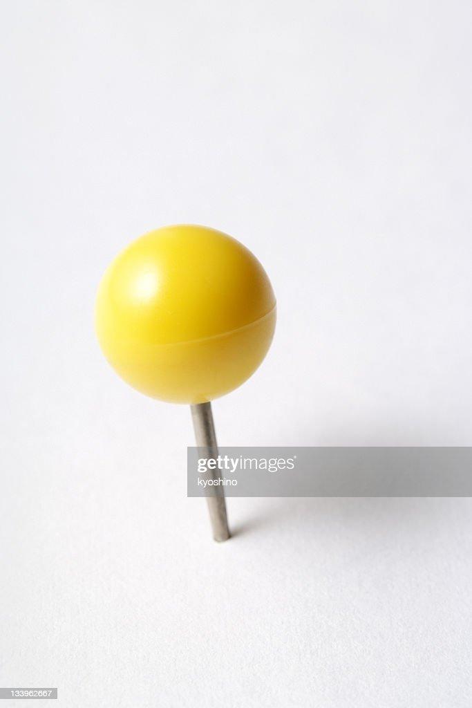 Isolated shot of yellow thumbtack on white background