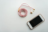 isolated smartphone with pink earphone