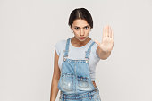 Isolated studio shot on gray background. Young annoyed  woman with bad attitude making stop gesture with her palm outward, saying no, expressing denial or restriction.