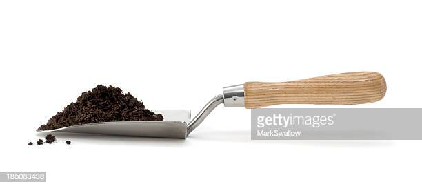Isolated trowel with pile of compost