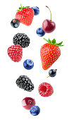Isolated berries. Falling blueberry, blackberry, raspberry, strawberry, black currants and cherry fruits isolated on white background with clipping path