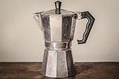 Picture of an old and used Italian espresso coffee machine of Moka pot style standing on a vintage wooden table, facing a white background