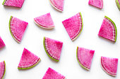Isolated watermelon radish slices. Colorful pink pieces on white background.