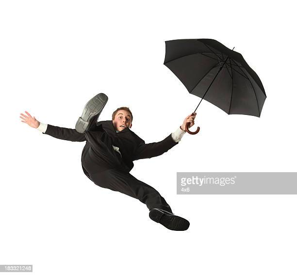 Isolated young businessman free falling while holding an umbrella