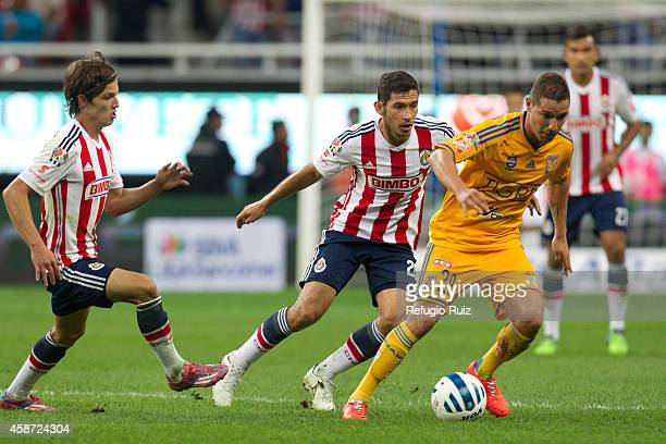 Israel Castro of Chivas fights for the ball with Jesus Dueñas of Tigres during a match between Chivas and Tigres UANL as part of 16th round Apertura...