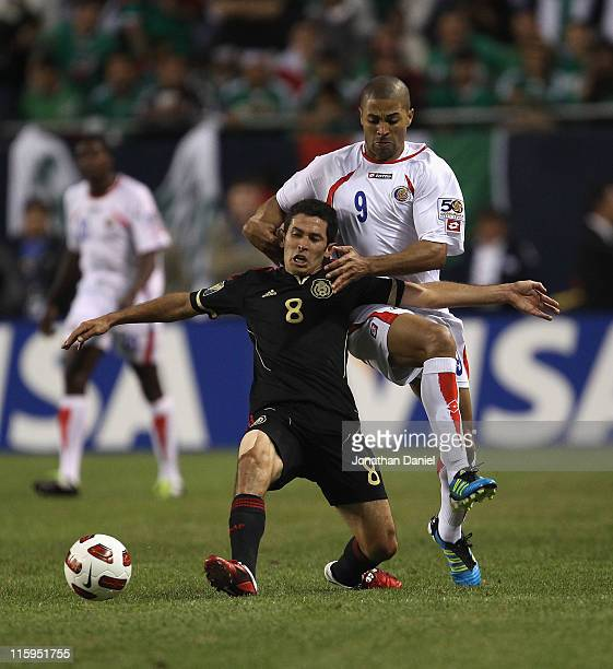 Israel Castro of Mexico is grabbed by Alvaro Saborio of Costa Rica during a CONCACAF Gold Cup 2011 match at Soldier Field on June 12 2011 in Chicago...