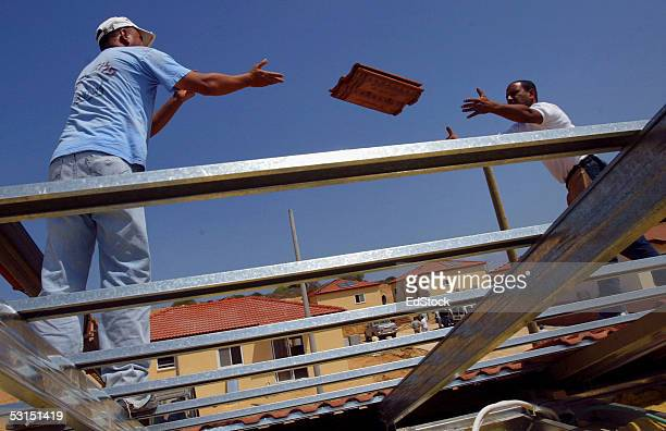 Construction workers place tiles on a roof at the area where Israel is building a temporary neighbourhood for settlers who are about to be evacuated...