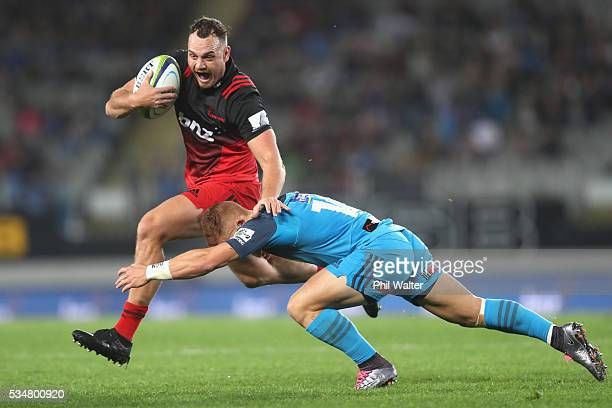 Israel Dagg of the Crusaders is tackled by Ihaia West of the Blues during the round 14 Super Rugby match between the Blues and the Crusaders at Eden...