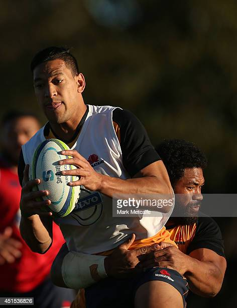 Israel Folau is tackled by Tatafu Polota Nau during a Waratahs Super Rugby training session at Kippax Lake on July 1 2014 in Sydney Australia