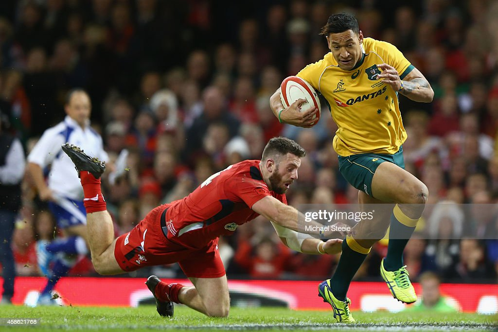 Israel Folau of Australia escapes the challenge of Alex Cuthbert of Wales to score his sides opening try during the International match between Wales...