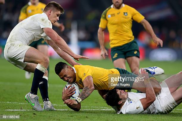 Israel Folau of Australia is hauled down by Owen Farrell of England and Brad Barritt of England during the 2015 Rugby World Cup Pool A match between...