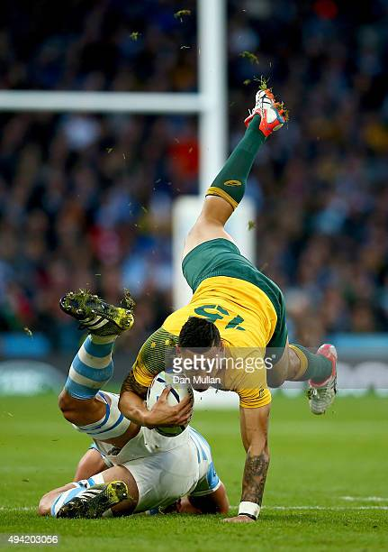 Israel Folau of Australia takes a tumble as he is tackled during the 2015 Rugby World Cup Semi Final match between Argentina and Australia at...
