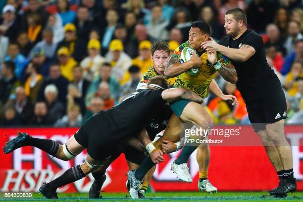 Israel Folau of Australia's Wallabies is tackled by Sam Cane of New Zealand's All Blacks and teammate Dane Coles during the Bledisloe Cup...