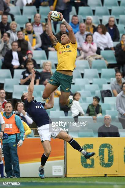 Israel Folau of the Wallabies catches a kick over Greig Tonks of Scotland to score a try during the International Test match between the Australian...
