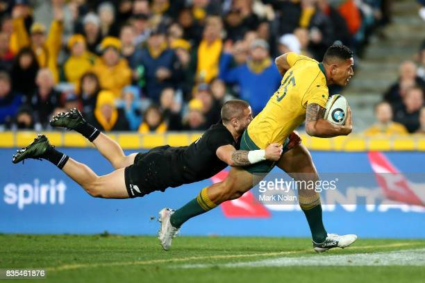 Israel Folau of the Wallabies heads to the try line to score as TJ Perenara of the All Blacks dives to tackle him during The Rugby Championship...