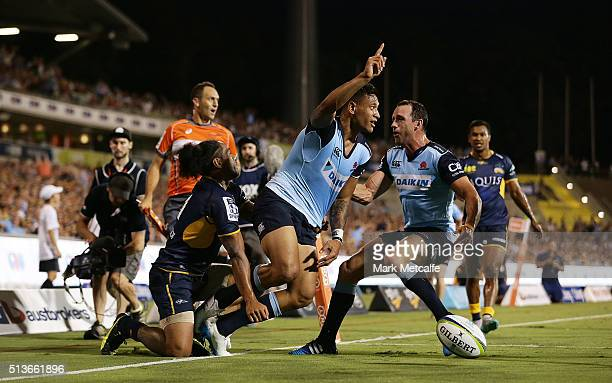 Israel Folau of the Waratahs celebrates scoring a try with team mate Matt Carraro during the round two NRL match between the Brumbies and the...