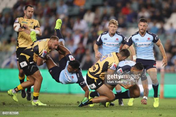 Israel Folau of the Waratahs is tackled by Jermaine Ainsley of the Force during the round one Super Rugby match between the Waratahs and the Force at...