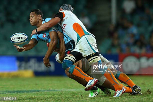 Israel Folau of the Waratahs offloads the ball in a tackle during the round five Super Rugby match between the Waratahs and the Cheetahs at Allianz...