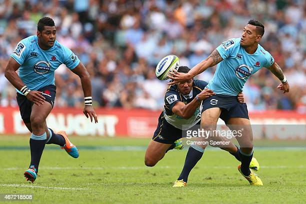 Israel Folau of the Waratahs offloads the ball in a tackle during the round six Super Rugby match between the Waratahs and the Brumbies at Allianz...
