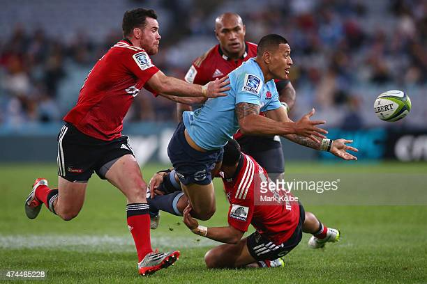Israel Folau of the Waratahs passes as he is tackled during the round 15 Super Rugby match between the Waratahs and the Crusaders at ANZ Stadium on...