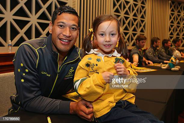 Israel Folau poses with a fan during the Australian Wallabies Fan Day at Brisbane City Hall on June 18 2013 in Brisbane Australia