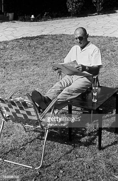 Israel in July 1967 Moshe Dayan in his garden his house has Zahala in the suburbs of Tel Aviv sitting on a garden chair feet on another chair reading...