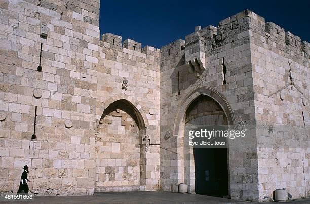 Israel Jerusalem The Jaffa Gate Orthodox Jewish man walking next to stone walls towards gate