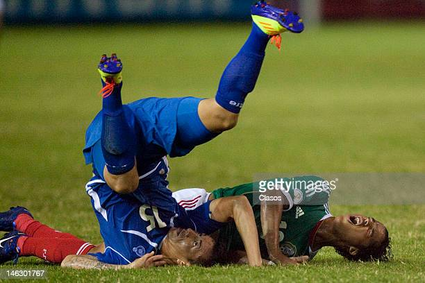 Israel Pacheco of El Salvador and Giovani Dos Santos of Mexico fight for a ball during a match between El Salvador and Mexico at Cuscatlan Staduim as...