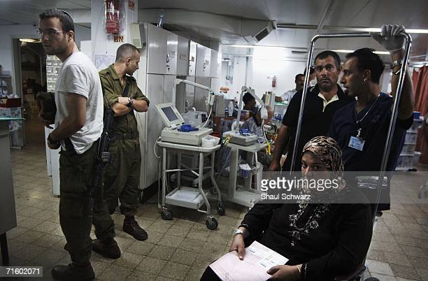 Israel soldiers await their injured colleague as a woman in a wheelchair waits to be check out of the hospital in an emergency room on August 7 2006...