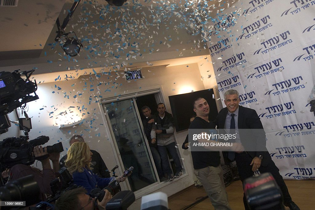 Israeli actor, journalist and author Yair Lapid, leader of the Yesh Atid (There is a Future) party, is received by supporters early on January 23, 2013 at his party headquarters in Tel Aviv. Israeli Prime Minister Benjamin Netanyahu said it was necessary to form the 'broadest possible government' after his Likud-Beitenu list won a narrow election victory, with the centrist Yesh Atid in second place. AFP PHOTO/AHMAD GHARABLI