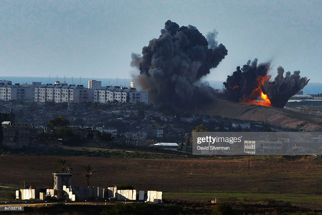 Israeli Air Force bombs explode on Palestinian targets in the northern Gaza Strip January 1, 2009 as seen from Israel's border with the Hamas-run territory. Israel continues to reinforce its troops amid talks of an internationally-brokered ceasefire. In the foreground is an Israeli army guard tower that overlooks the border with Gaza.