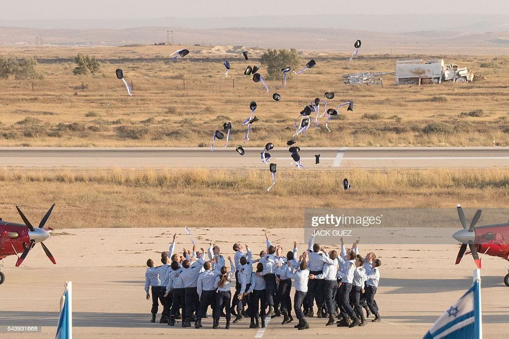Israeli Air Force pilots throw their hats in the air as they celebrate their graduation during a ceremony at the Hatzerim base in the Negev desert, near the southern Israeli city of Beer Sheva, on June 30, 2016. / AFP / JACK