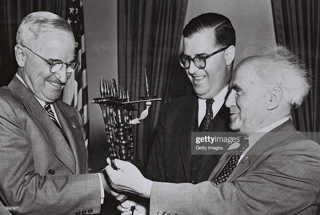 Israeli ambassador to the United States Abba Eban looks on as Israeli Prime Minister David BenGurion gives a present to US President Harry Truman...