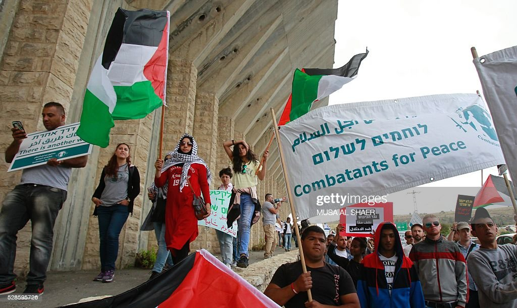 Israeli and Palestinian peace activists carry placards as they wave a Palestinian national flag during a peace march at an Israeli road near a checkpoint between the West Bank city of Beit Jala and Jerusalem, on May 6, 2016. / AFP / MUSA