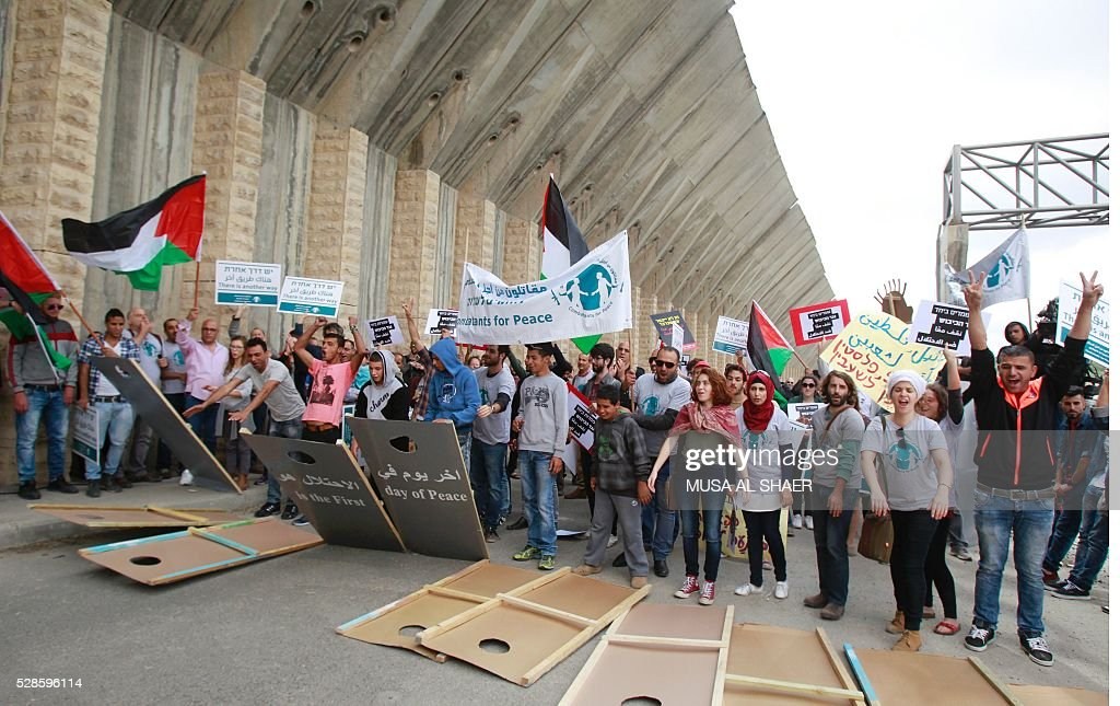 Israeli and Palestinian peace activists drop and step on cardboard cut-outs depicting the Israeli controversial separation wall as they wave a Palestinian national flag during a peace march at an Israeli road near a checkpoint between the West Bank city of Beit Jala and Jerusalem, on May 6, 2016. / AFP / MUSA