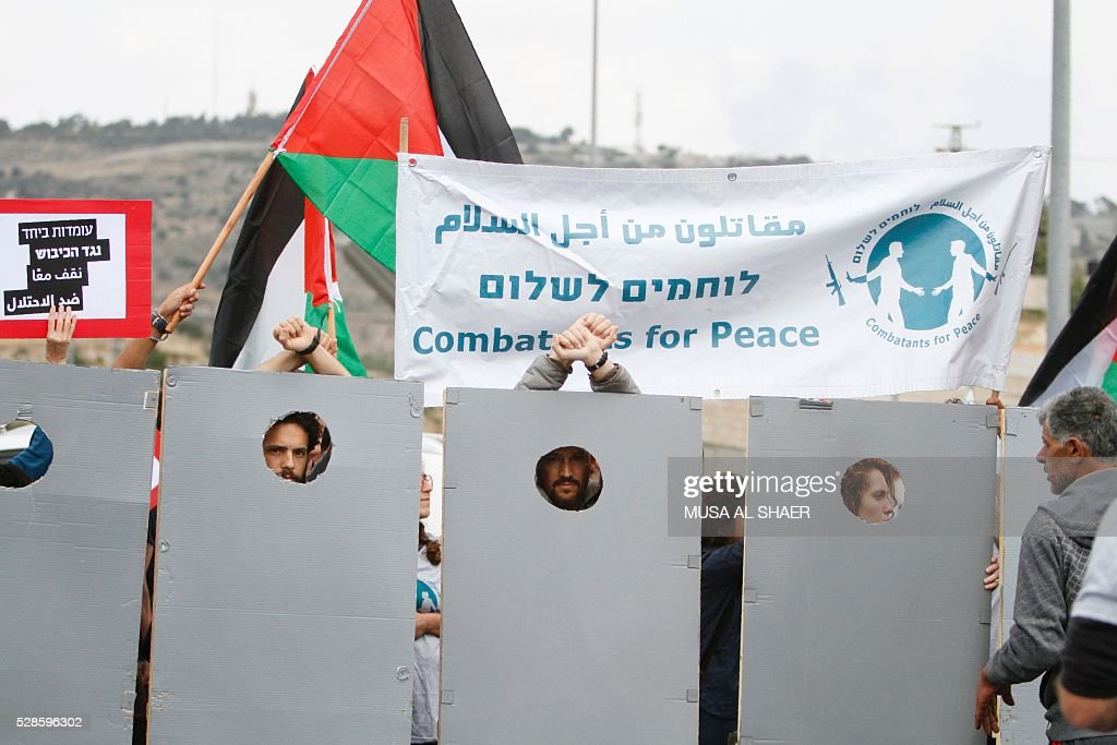 Israeli and Palestinian peace activists stand behind cardboard cut-outs depicting the Israeli controversial separation wall as they wave a Palestinian national flag during a peace march at an Israeli road near a checkpoint between the West Bank city of Beit Jala and Jerusalem, on May 6, 2016. / AFP / MUSA
