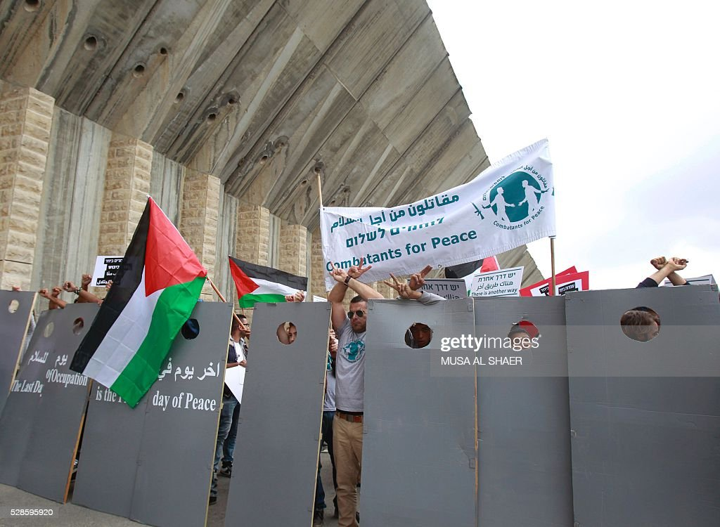 Israeli and Palestinian peace activists stands behind cardboard cut-outs depicting the Israeli controversial separation barrier as they wave a Palestinian national flag during a peace march at an Israeli road near a checkpoint between the West Bank city of Beit Jala and Jerusalem on May, on May 6, 2016. / AFP / MUSA