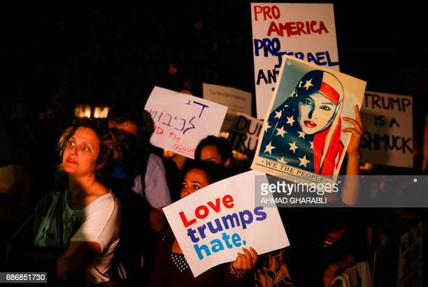 Israeli and US protesters hold up placards and shout slogans during a demonstration against the ongoing visit of the US president to Israel on May 22...