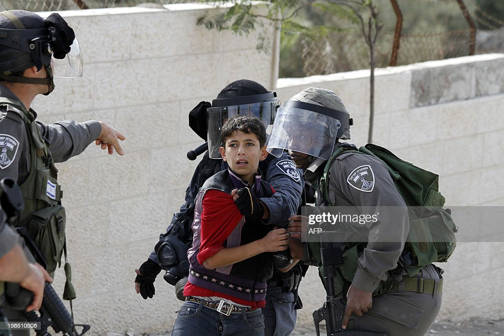 Israeli anti-riot policemen detain a Palestinian boy during a protest in Aida refugee camp near the West Bank city of Bethlehem on November 16, 2012. Thousands of angry Palestinians rallied across the West Bank, urging Hamas militants to 'bomb Tel Aviv' as Israel pursued a relentless air campaign on the Gaza Strip. AFP PHOTO/MUSA AL SHAER