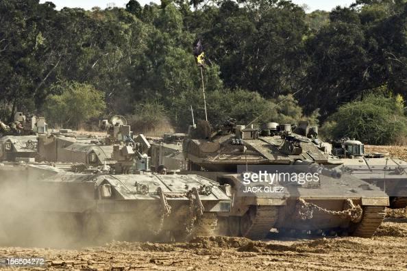 Israeli APC armored personnel and an Israeli Merkava tank are stationed at the IsraeliGaza Strip border on November 16 2012 Israeli officials said...