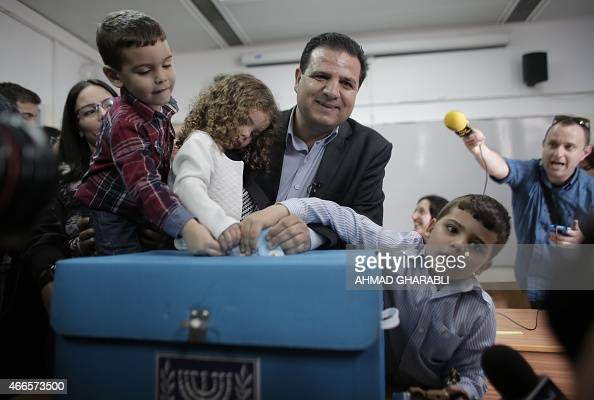Israeli Arab political leader and head of a joint list of Arab parties Ayman Odeh casts his ballot with his children at a polling station in the...