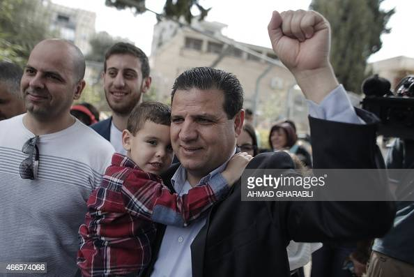 Israeli Arab political leader and head of a joint list of Arab parties Ayman Odeh gestures as he carries his son after casting his ballot at a...