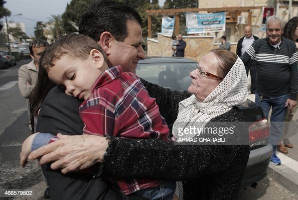 Israeli Arab political leader and head of a joint list of Arab parties Ayman Odeh is greeted by a supporter as he carries his son after casting his...