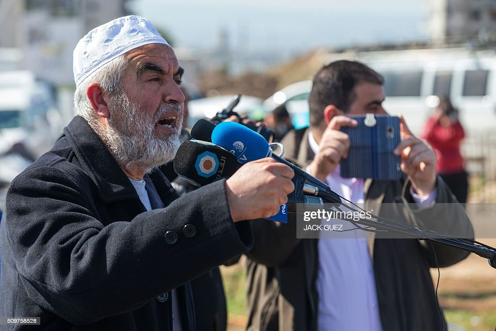 Israeli Arabs and Sheikh Raed Salah (L), the leader of the radical northern wing of the Islamic Movement in Israel, speaks as he attends a prayer in support for the release of Mohammed al-Qiq, a Palestinian prisoner on hunger strike, outside the hospital where he is being treated in the northern Israeli town of Afula on February 12, 2016. Ailing Palestinian journalist Qiq will keep up his ten-week hunger strike despite Israel suspending a detention without trial order against him, his lawyer said. / AFP / JACK GUEZ