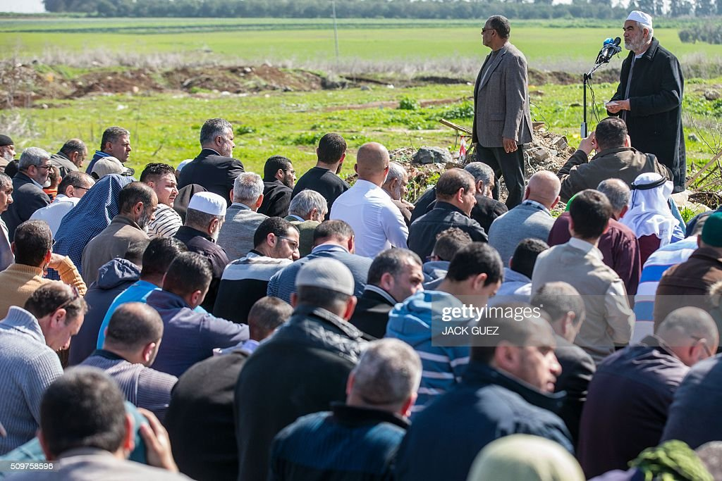 Israeli Arabs and Sheikh Raed Salah (R), the leader of the radical northern wing of the Islamic Movement in Israel, attends a prayer in support for the release of Mohammed al-Qiq, a Palestinian prisoner on hunger strike, outside the hospital where he is being treated in the northern Israeli town of Afula on February 12, 2016. Ailing Palestinian journalist Qiq will keep up his ten-week hunger strike despite Israel suspending a detention without trial order against him, his lawyer said. / AFP / JACK GUEZ